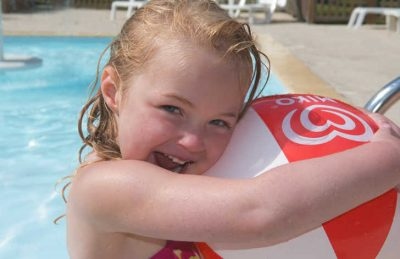 A young girl with a beach ball at the campsite swimming pool