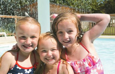 Three girls having fun at the campsites swimming pool
